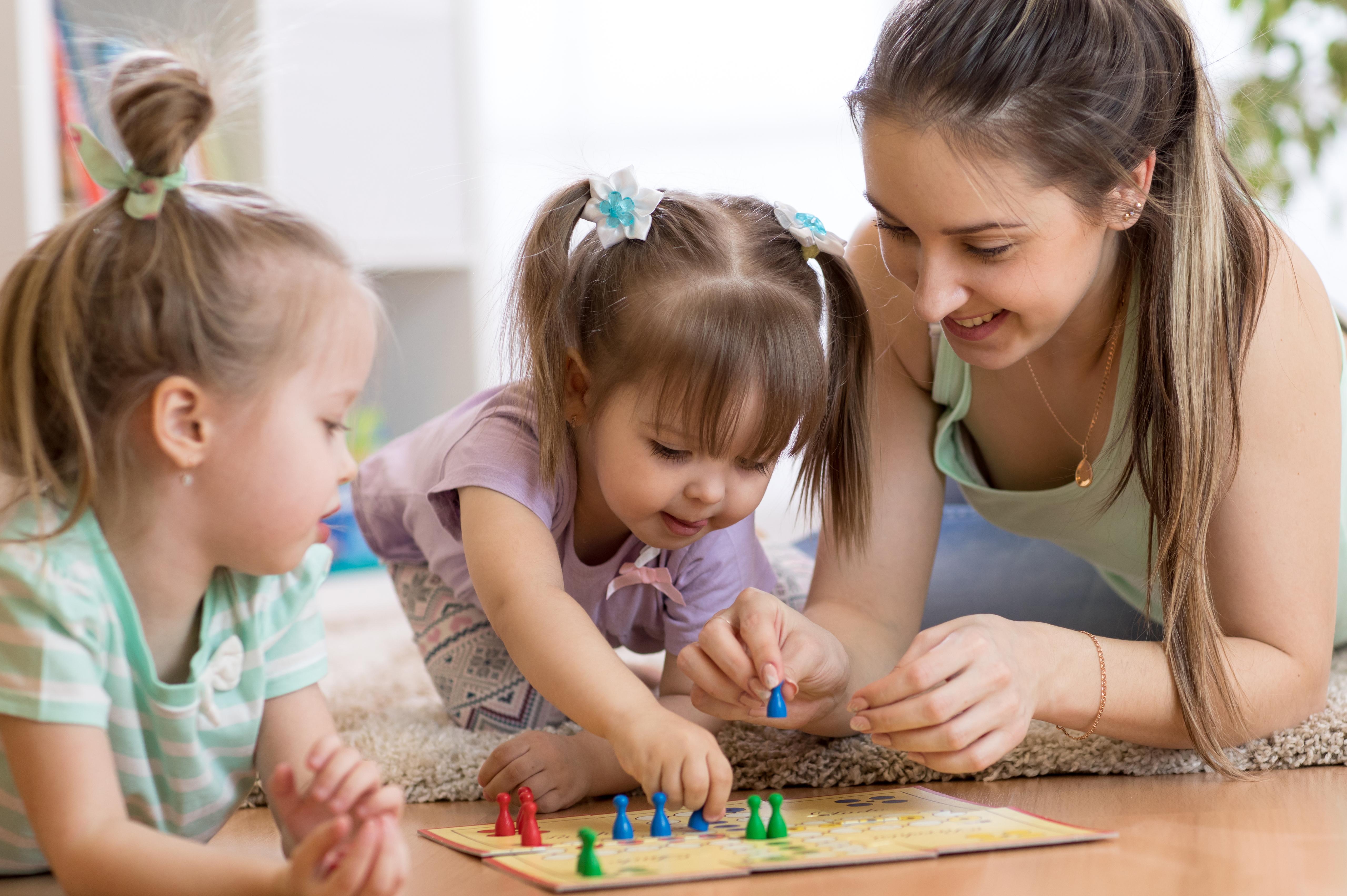 Gyerekek társasjátékoznak az anyukájukkal