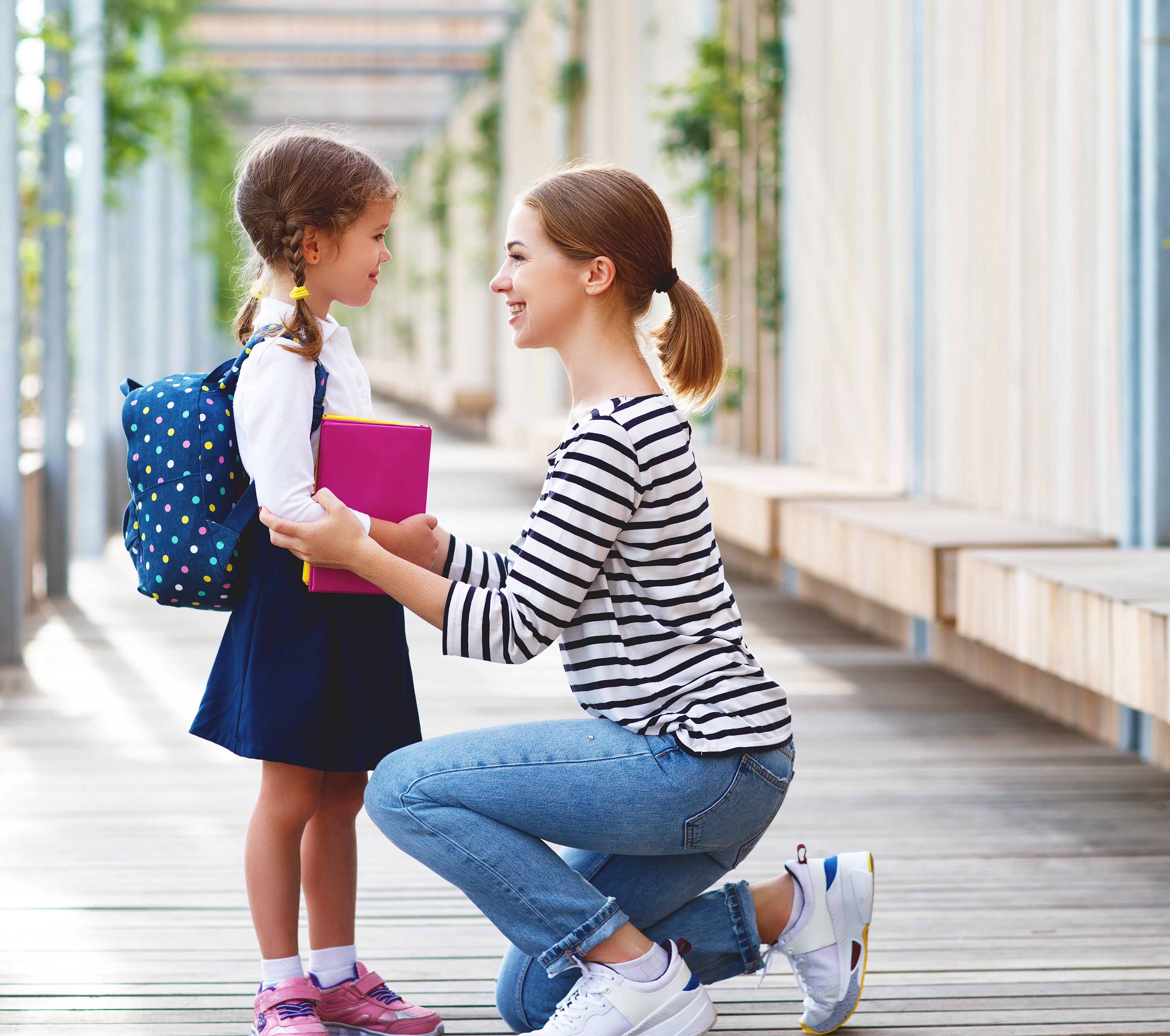 Kislány elköszön az anyukájától az iskola ajtajában