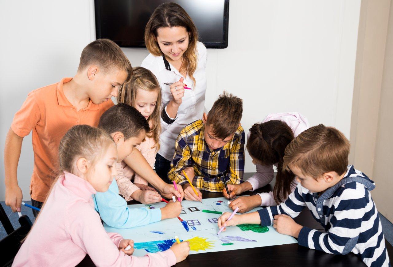 Gyerekek rajzolnak a tanítónővel