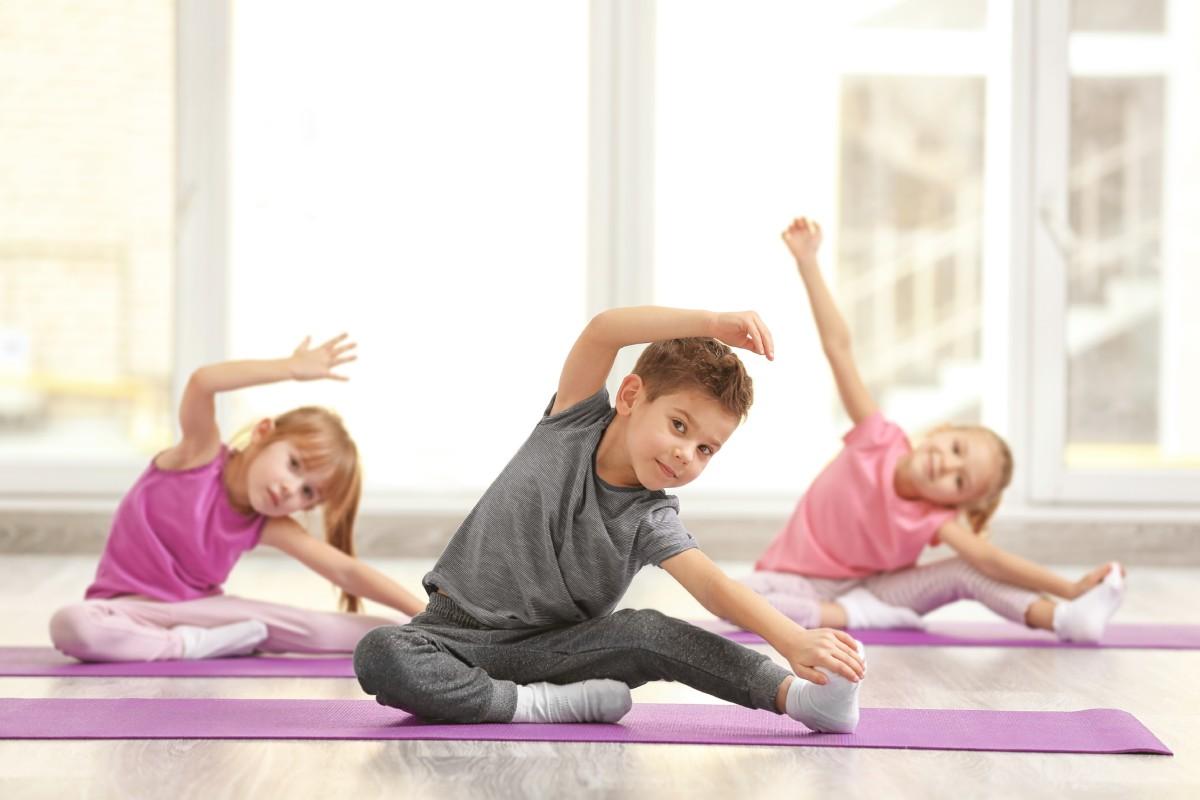 Gyerekek nyújtanak jóga matracon
